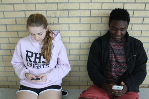 A common sight in many high schools, two students sitting together but too distracted by their phones to even look up.