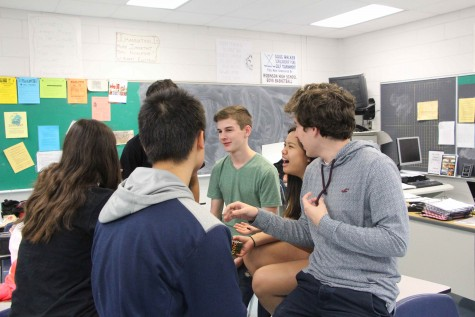 A group of sophomore students excitedly chit chat during lunch, exchanging drama.