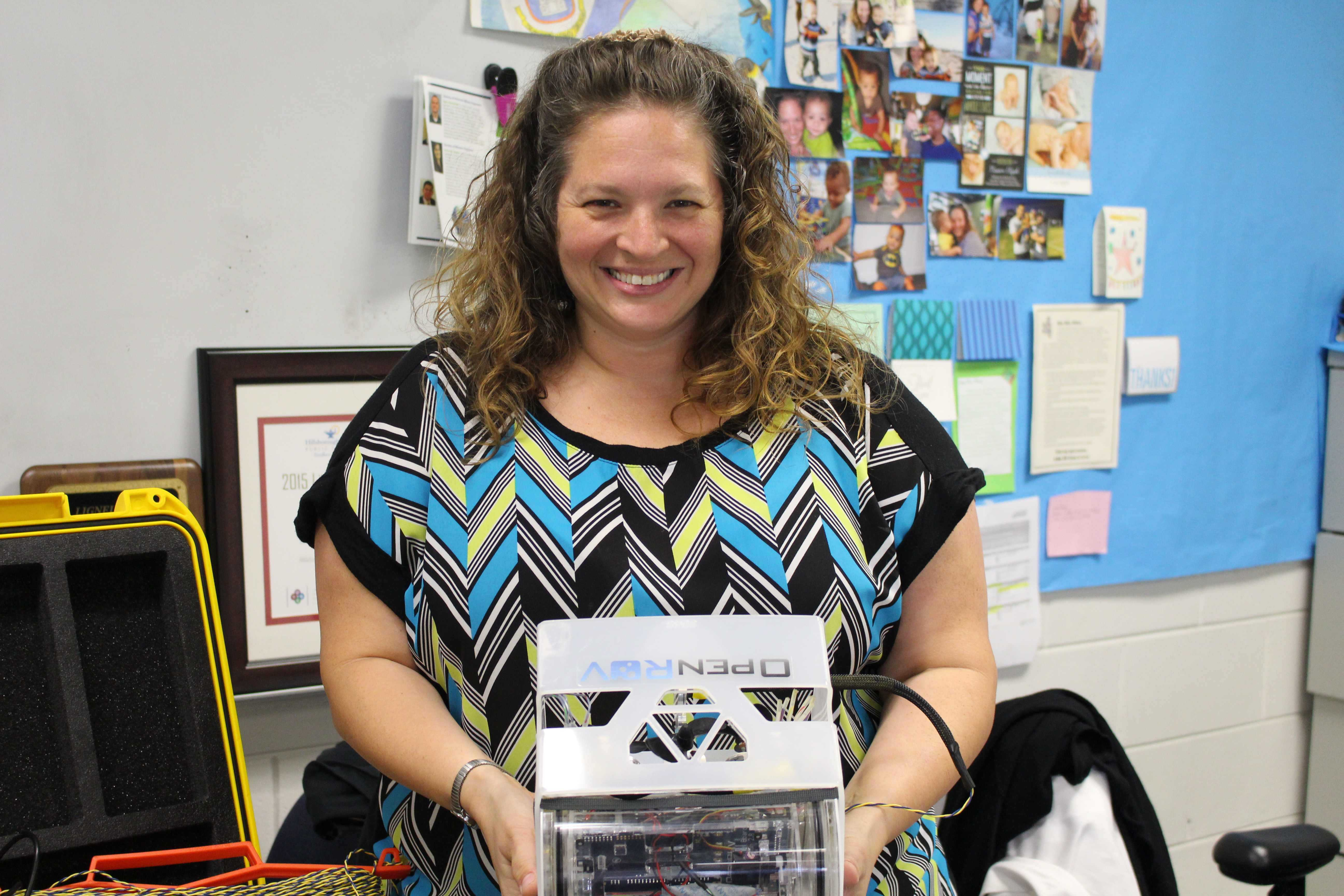 Here, IB Biology teacher Tiffany Oliver is featured with an underwater ROV robot she built during a STEM camp.