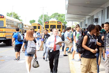 Mr. Brian Hoover makes his way through bus rider traffic after school to make students aware of changes in their bus schedules.