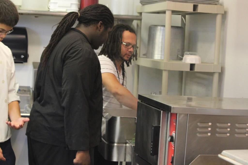 Chef Clarke shows one of his students how to properly use the tilt skillet.