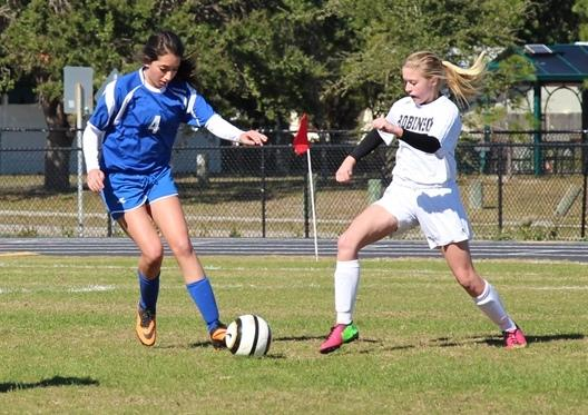 Freshman Knight Maggie O'Brien passing the ball past a Seminole defender.