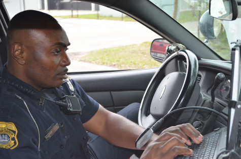 Officer Lucas, the Student Resource Officer (SRD) for Robinson High School, works on my police report.
