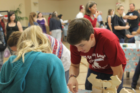 At the Shriner's Hospital Holiday party, Alexander Wilsey ('15) helps children create crafts. The RHS Strong Legs club had a table at the party with different holiday themed crafts available to decorate.