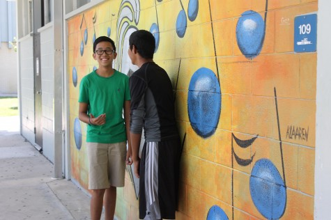 Students converse by the mural  by the band room.