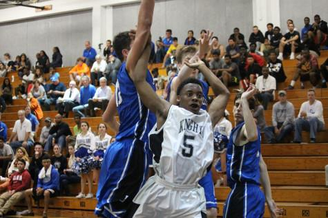 Iyan Mitchell ('15) blocks Jesuit's players. Mitchell lead the team with 14 points.