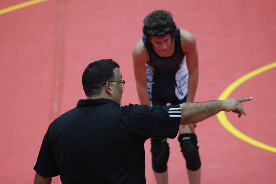 Coach Montero instructs a wrestler during a break in the match.