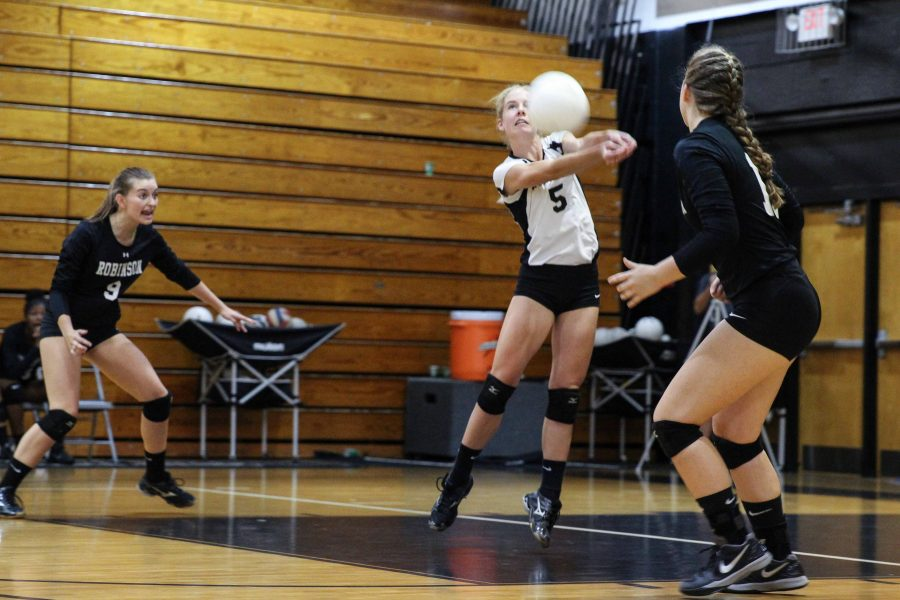 Captain and libero Emily Draper ('17) digs as teammates Laura Hill ('17) and Kristin Werdine ('19) standby.