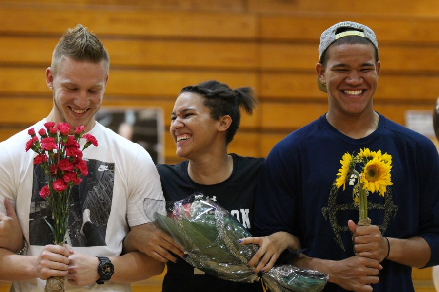 With brothers Thomas (left) and Malik (right) escorting her, McKenna Tyson ('17) walks down the court during senior night celebrations before Robinson's game against Durant.
