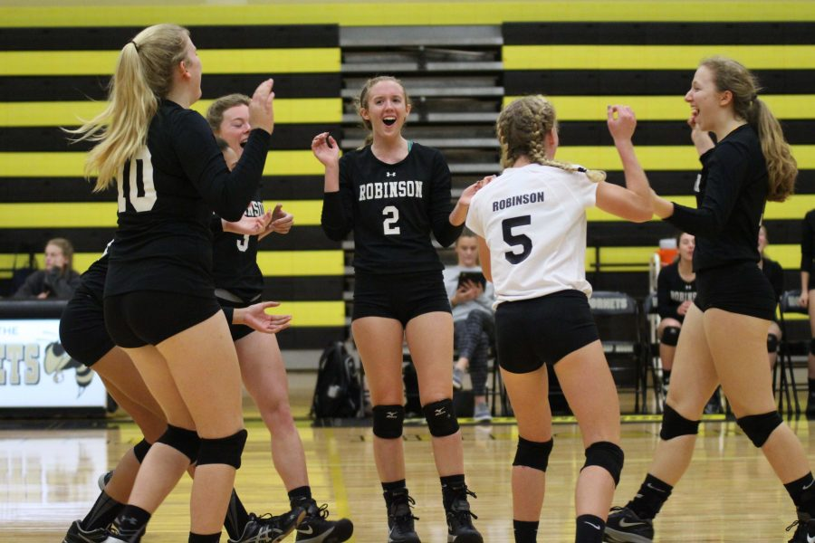 The team celebrates after scoring a point in the second set.