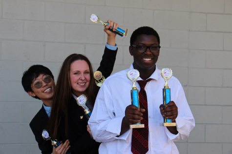 Club members Dongwoo Kim ('19), Hayle Short ('19), and  Mekhi Cusseaux ('19) pose with their trophies.