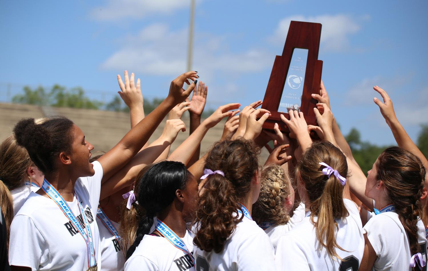The team holds up the state championship trophy during the final cheer of the season.