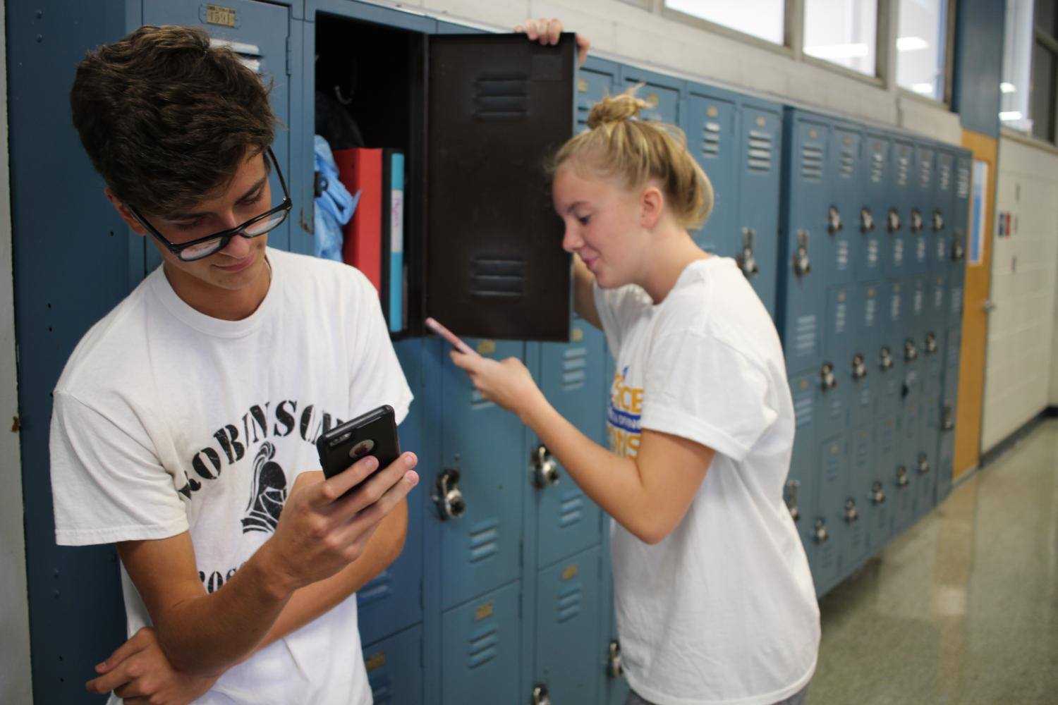 Abigail+Meyer+%28%2718%29+and+Andrew+McMillan+%28%2718%29+wait+in+the+halls+of+Robinson+on+their+cellphones.