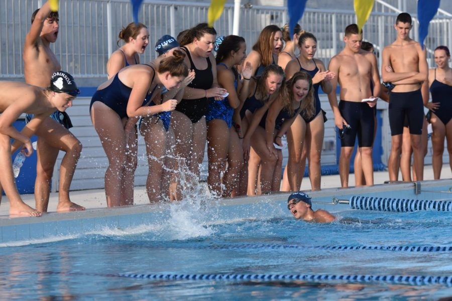 The swim team cheers on a swimmer at a recent swim meet.