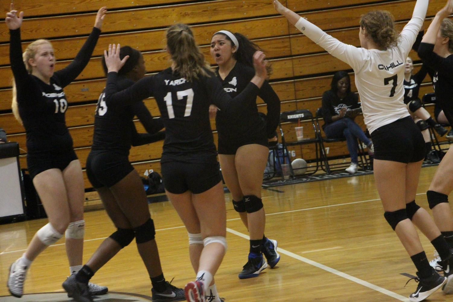 The Lady Knights celebrate as Lauren Johnson ('19) serves up an ace.