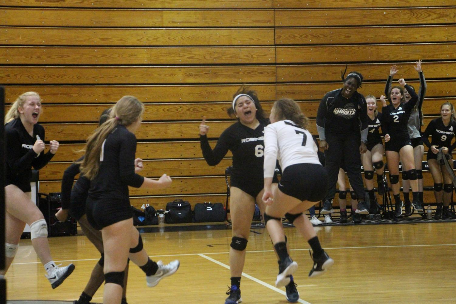 The Lady Knights cheer after Kristin Werdine ('19) attacks the ball for a kill in the third set.