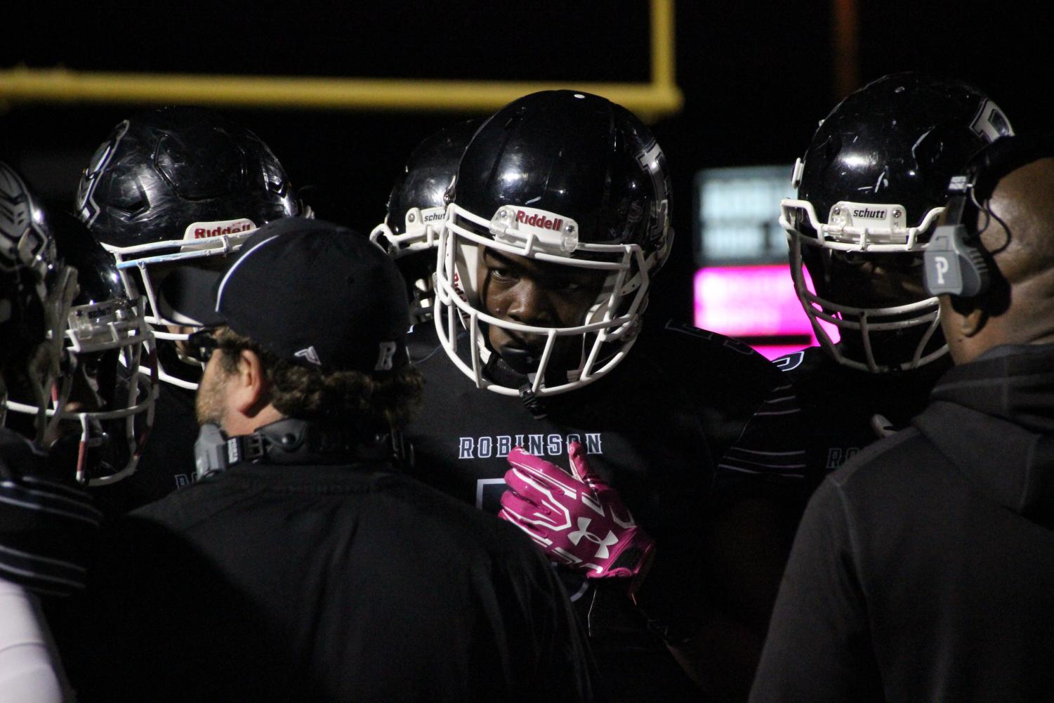 Quinton Lane '19  lines up in the huddle during the Jefferson vs. Robinson game last Friday night. The Knights face Bloomingdale tonight in the final game of the season.