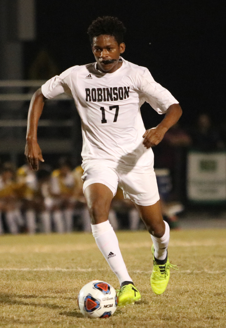 Senior Solomon Browne dribbles the ball up field in their game against Plant on Jan. 16.