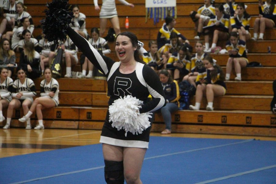 Mia Blumenthal ('19) encourages the crowd  to get loud during the cheering part of the performance.
