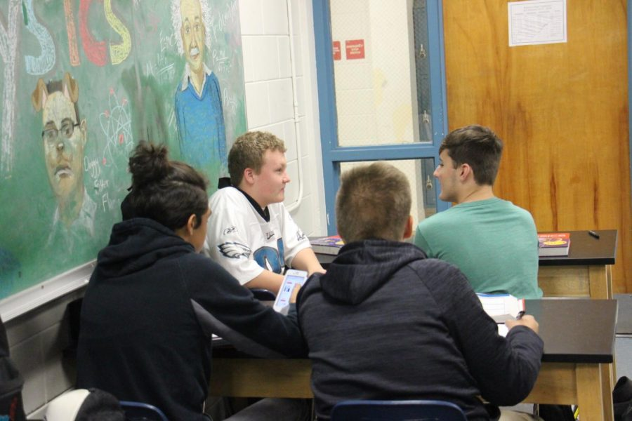 Lucas Long ('19), a student in the honors physics class, chats with his classmates while one substitute, of many, prepares to call roll.