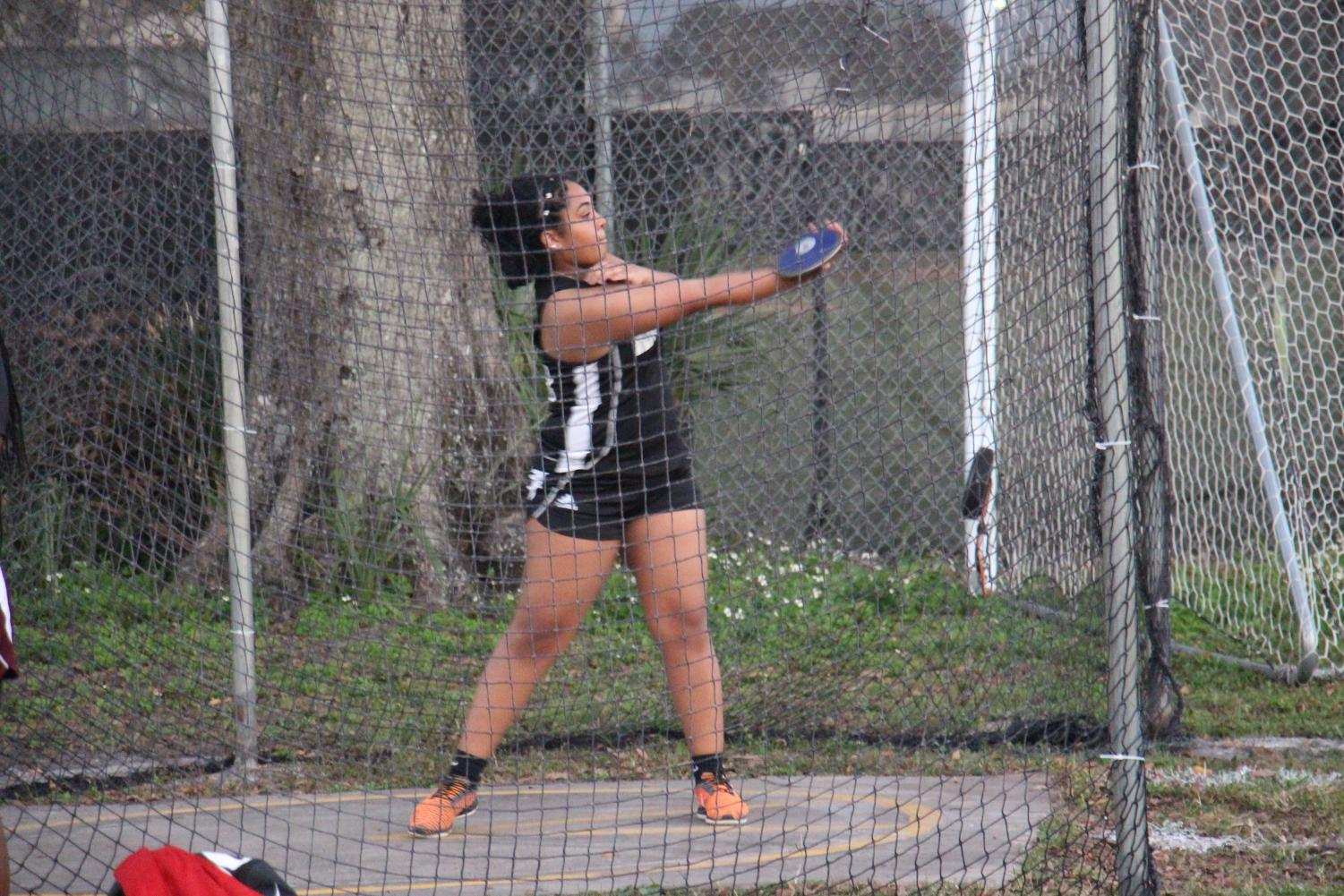 Danika Baro ('18) swings disc during her turn at the season opener at home, February 19.