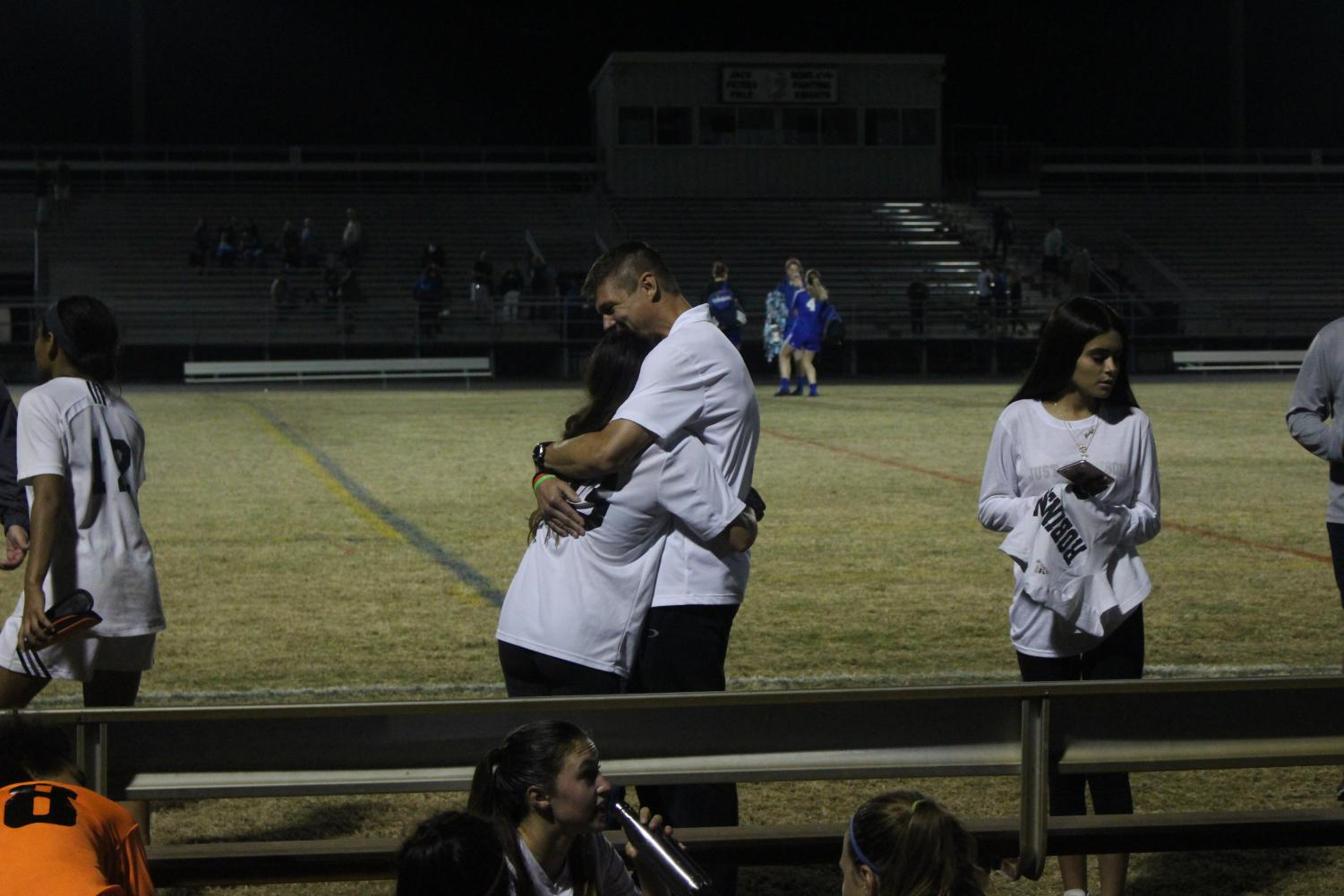 Captain Elisa Toghranegar ('18) hugs Helms in his last game coaching as the Lady Knights fall 3-0 to Osceola.
