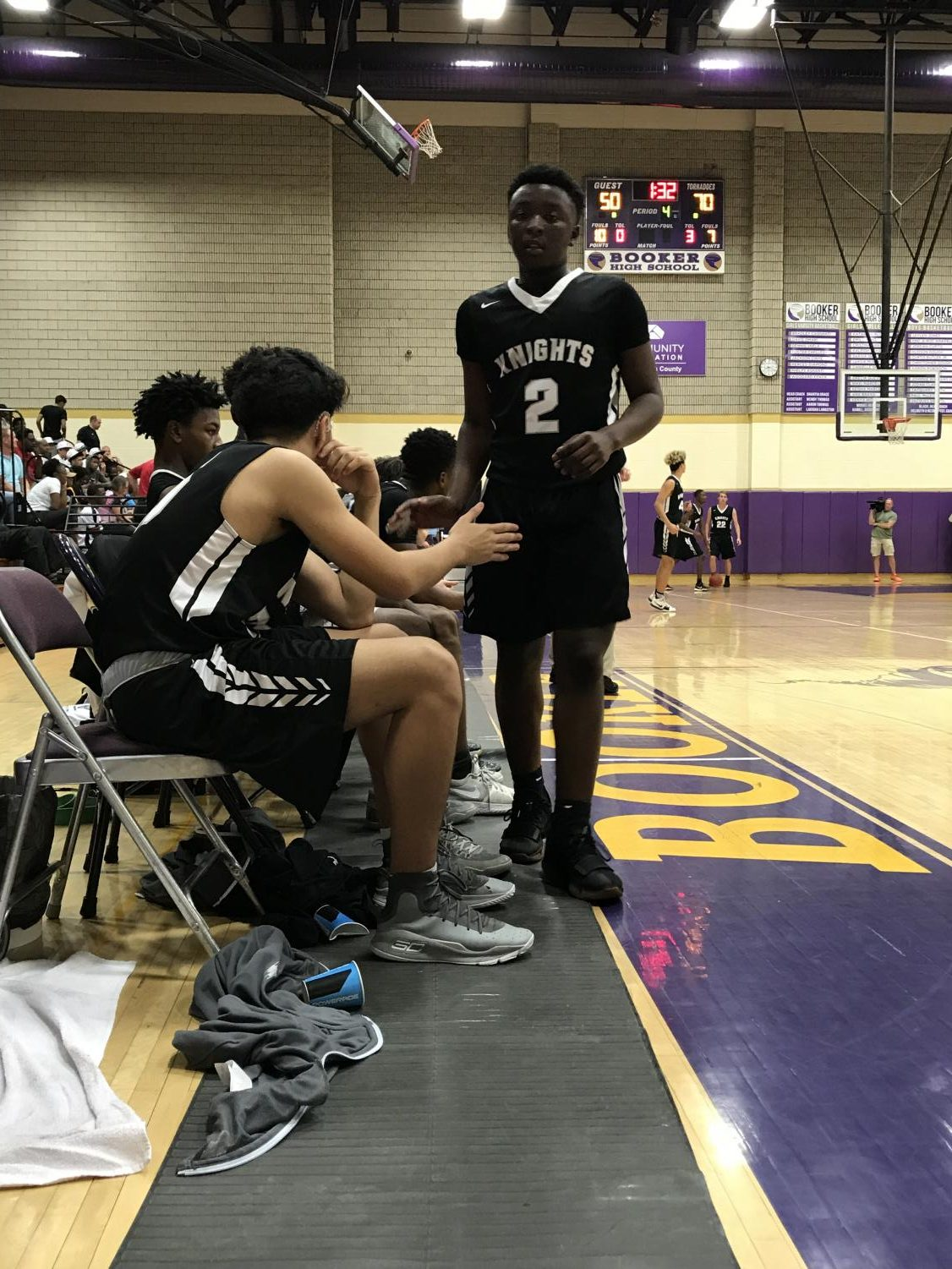 Point guard Tyrel Gray ('21) high-fives his teammates as he walks off the court for his last freshman game. Gray had six points and three assists in the Thursday loss to Booker.