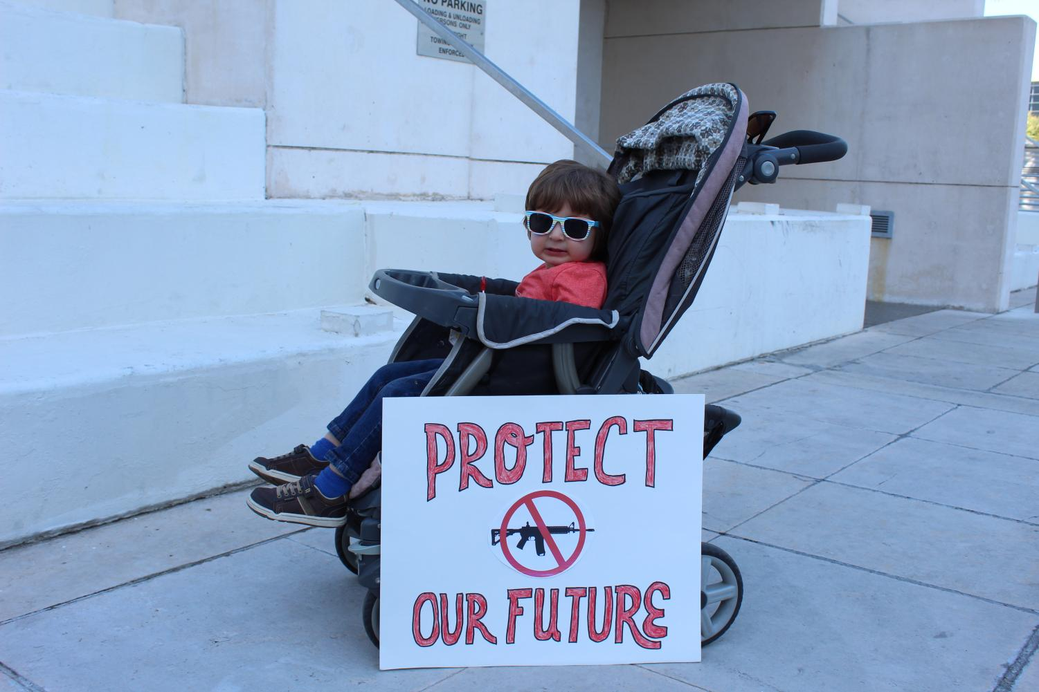 A mom places her sign in front of her child's stroller to add some emphasis on why she marches.