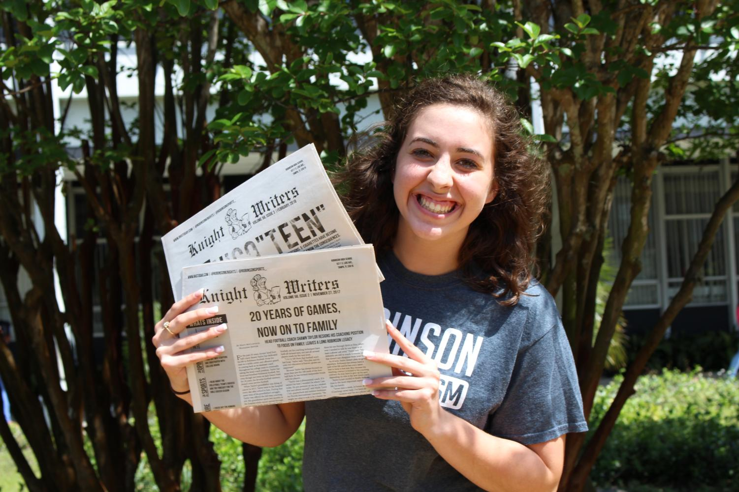 Anna Thomas ('18) poses with the second and third issues of Knight Writers for the 2017-18 year.