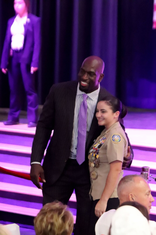 Professional wrestler and community advocate Titus O'Neil poses for a photo with a student.