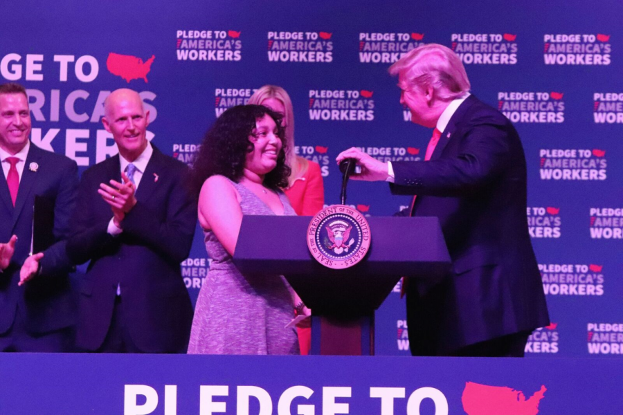 While shaking hands with Isabella Cruz, President Donald Trump introduces the upcoming senior to talk about her success at Tampa Bay Tech.