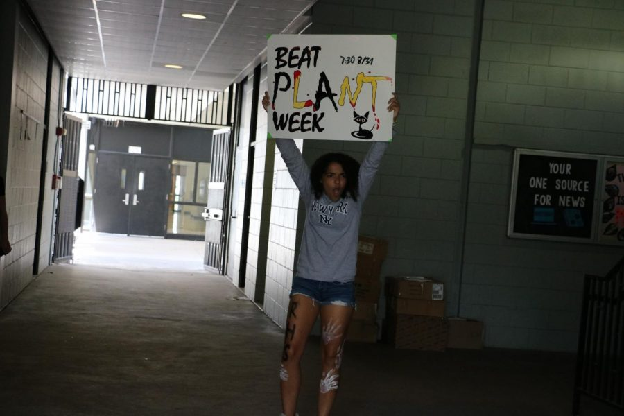 Natalia McCallaa ('20)  gets students pumped up for the pep rally in the hallway