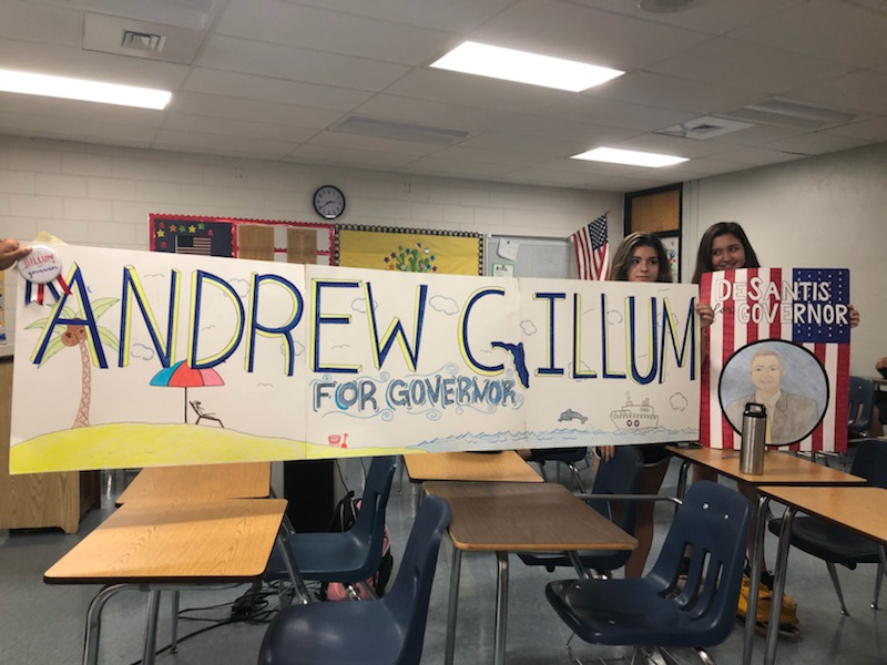 Three students display the political posters they made for their chosen candidate.