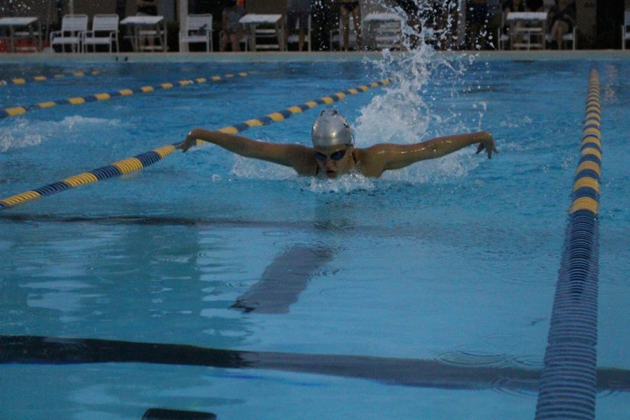 Maya Fisher ('20) races down the lane doing a butterfly stroke.