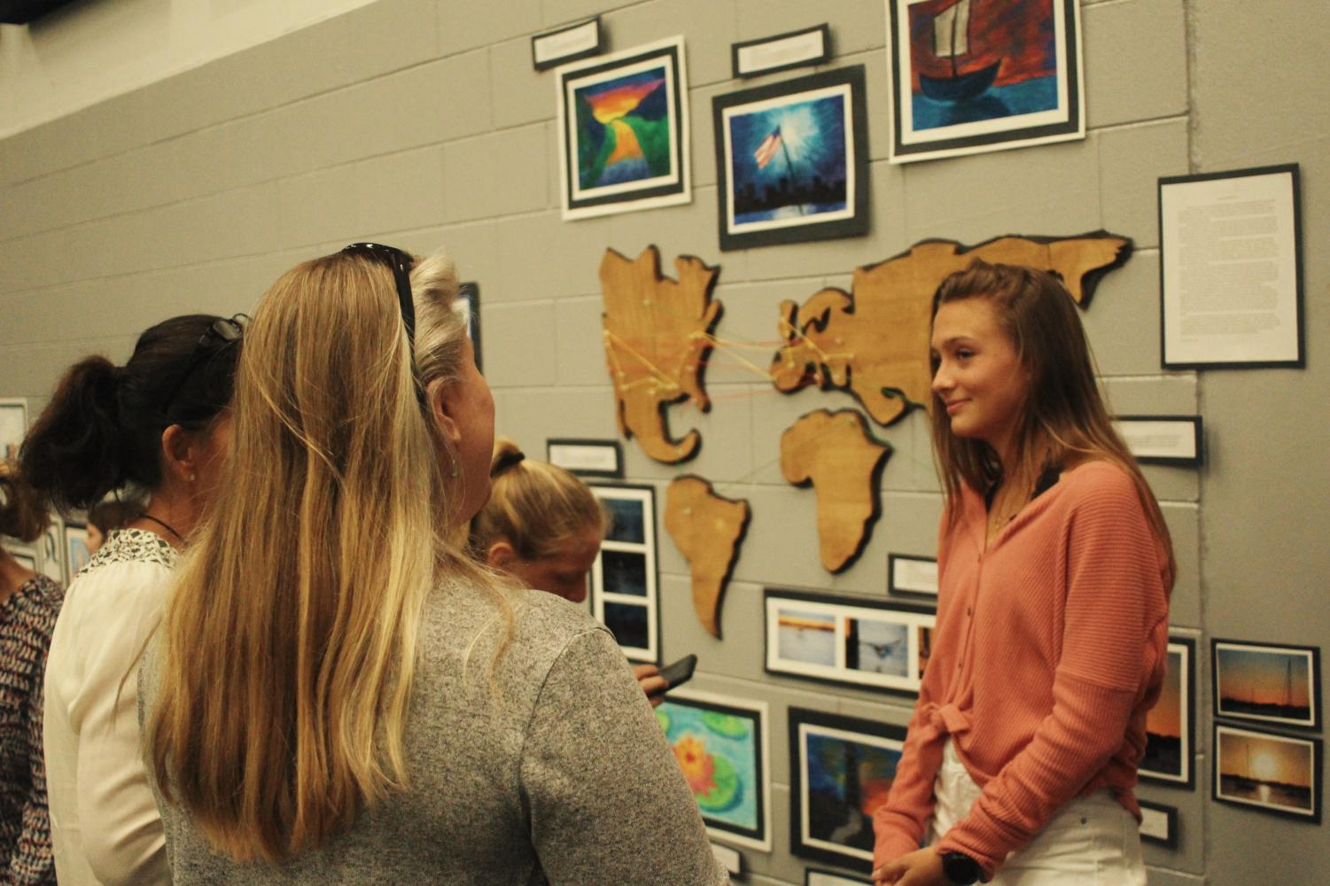 Artist Samantha Davidson ('19) carves out a map of the world and places string indicating where she's been and where she wants to go as the centerpiece of her exhibit. Davidson places three strings indicating places she has lived in, places she has been to, and places she wants to go to someday.
