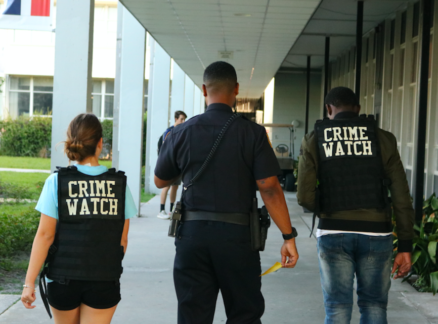 Officer Hester walks with students during the Crime Watch class.