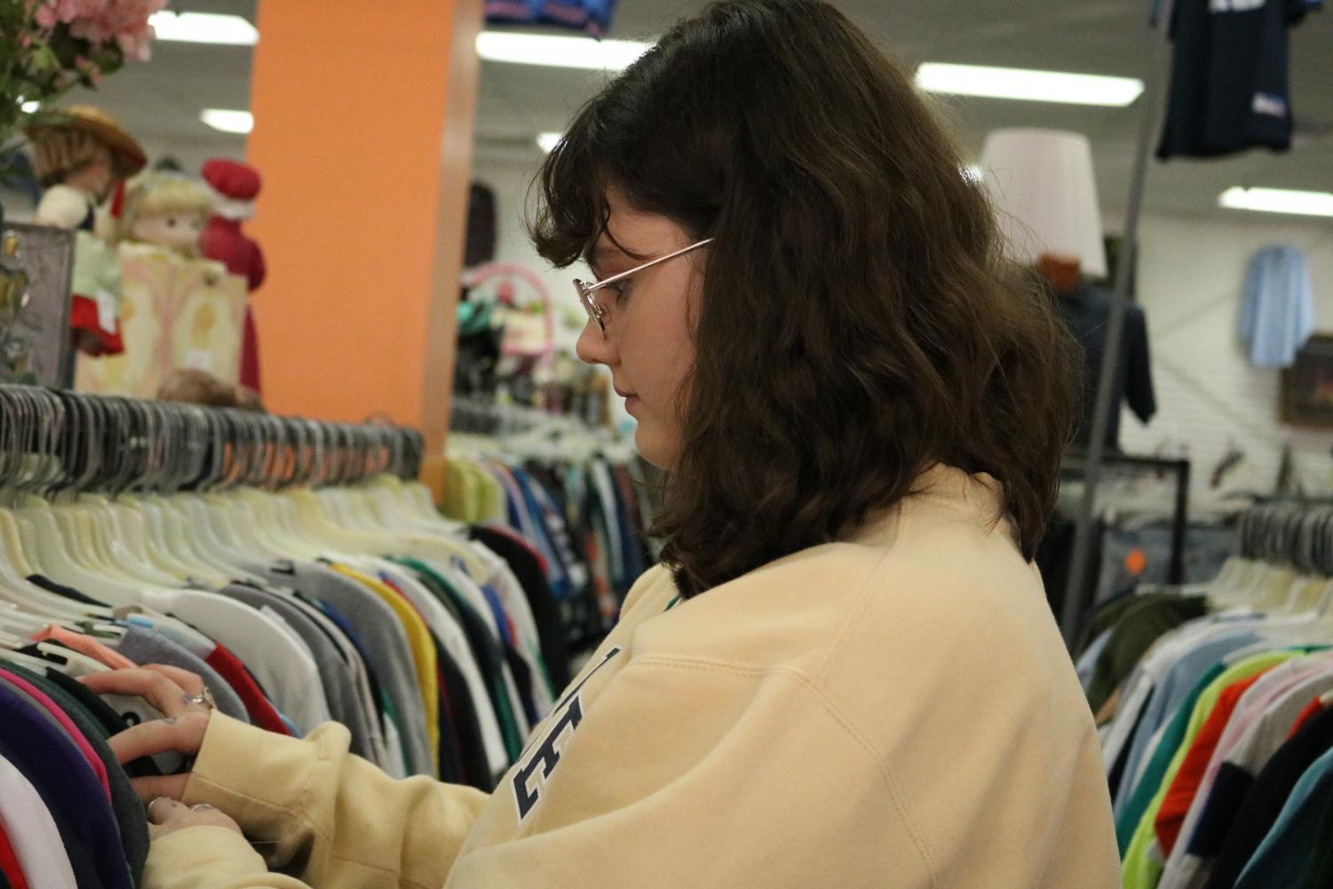 Lilly Brill ('21) looks at the men's t shirts section, a popular section to most Robinson Students.