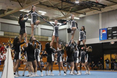 The cheer team collaborates to form a full pyramid as the flyers link arms in the air.