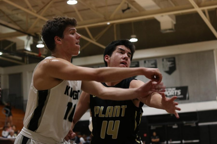 Zach Hearing ('20) battles for position with a Plant player.
