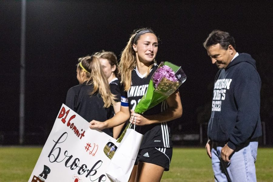 Head captain Brooke Volpi (20) walks the soccer field and is welcomed by her team.