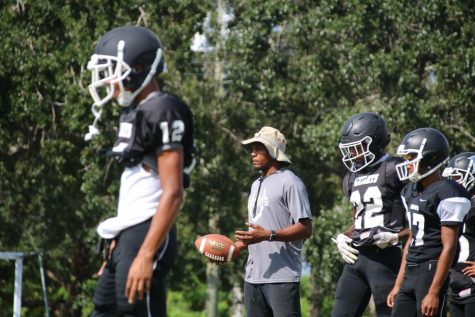 Frankie Williams coaches the football team at practice after school.