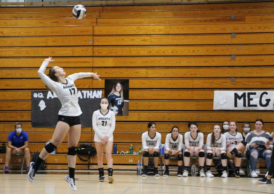 Mila Yarich ('21) serves the ball as her teammates watch nearby. Yarich, one of the team's captains, has committed to play volleyball at Yale University.