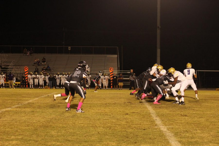 The Robinson Knights charge the football during the game against Booker, sporting pink socks and cleats for Pink Out for Breast Cancer Awareness Month.