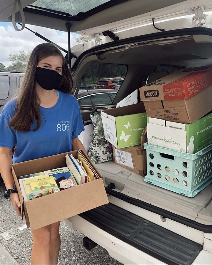 Ingram posing with books she collected in her October drive.