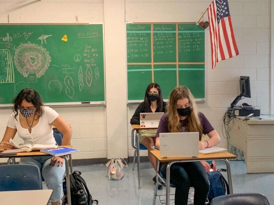 Adriana Navarrete ('23)(left), Celeste Lara ('23)(back) and Ava LeClair ('23) wearing masks in a classroom while socially distanced.