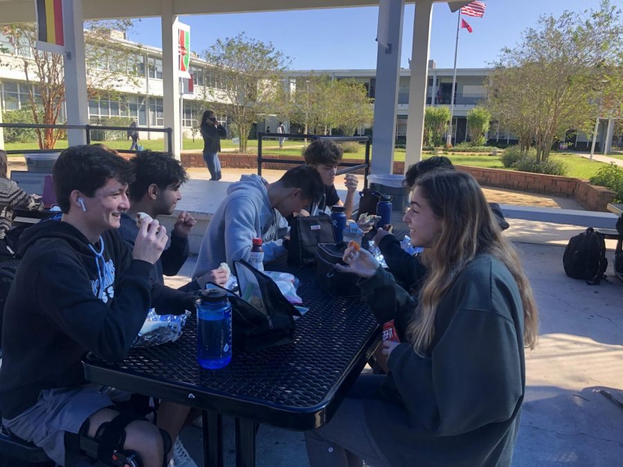 Owen Higgins ('21) (far left) socializes with his friends during lunch after returning for the second quarter.
