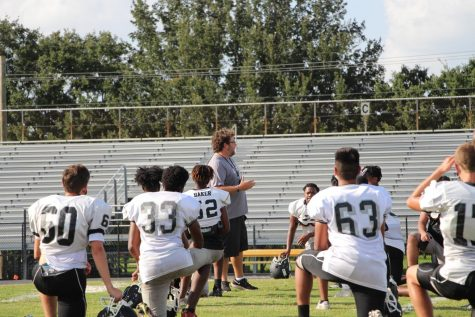 The football team surrounds Coach Everhart during a practice on Sept. 2.