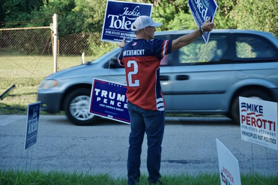A man holds sign displaying his support for local candidate Jackie Toledo.