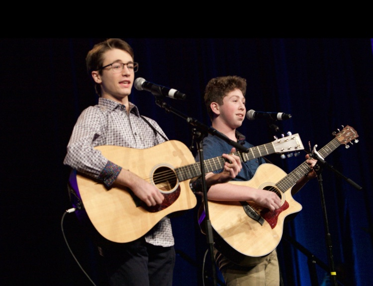 Jordan Schmidt (left) and Jacob Fishman (right) perform with guitars in hand. The two wrote and performed songs together, something that sparked Fishman's interest in producing his own music.