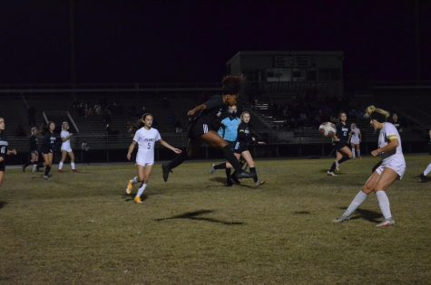 Williams flies into the air after kicking the ball, her eyes focused on the play.